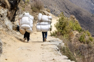 Two Sherpa Porters Carrying Heavy Sacks In The Himalaya At Evere
